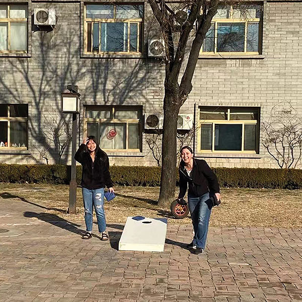 staff enjoying cornhole outdoors while restricted to campus