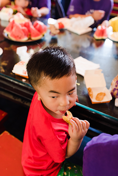 boy enjoying chicken nuggets with plate full of watermelon in background