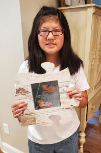 Zoey holding a photo of Stan holding her as an infant orphan