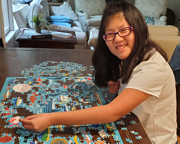 zoey is happily working a large puzzle