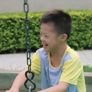 boy with down syndrome laughs while swinging