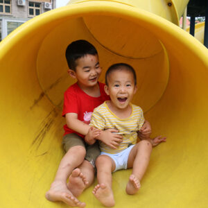 two boys laughing on slide