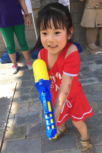 the water gun is almost bigger than her grin