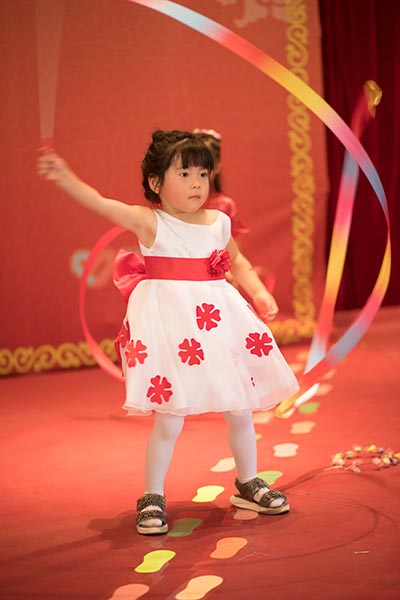 young orphan performs ribbon dance for children's day